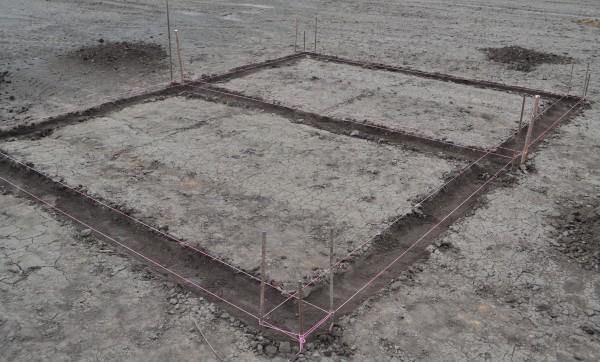 Разметка места под фундамент с использованием колышков и нити