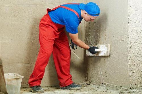 Процесс нанесения цементной смеси на стену.