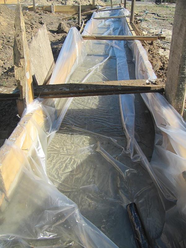 Гидроизоляция пленкой ленточного фундамента перед заливкой бетона.